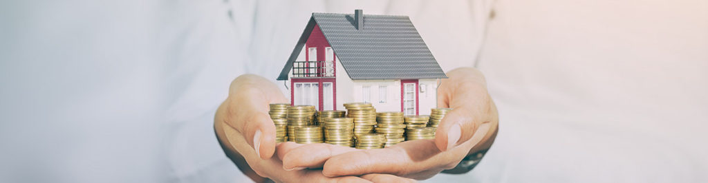 Haus mit Kleingeld in Hand