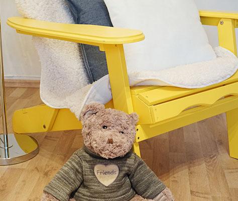 Teddybär vor gelbem Stuhl