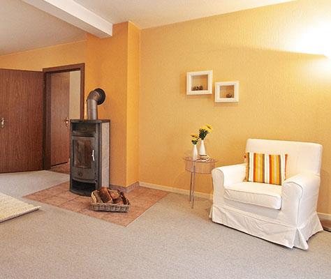 weißer Sessel vor Wand orange mit Kamin
